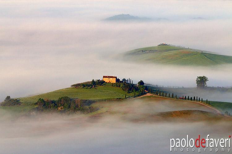 Een blik op de heuvels van Pienza op een nevelige ochtend