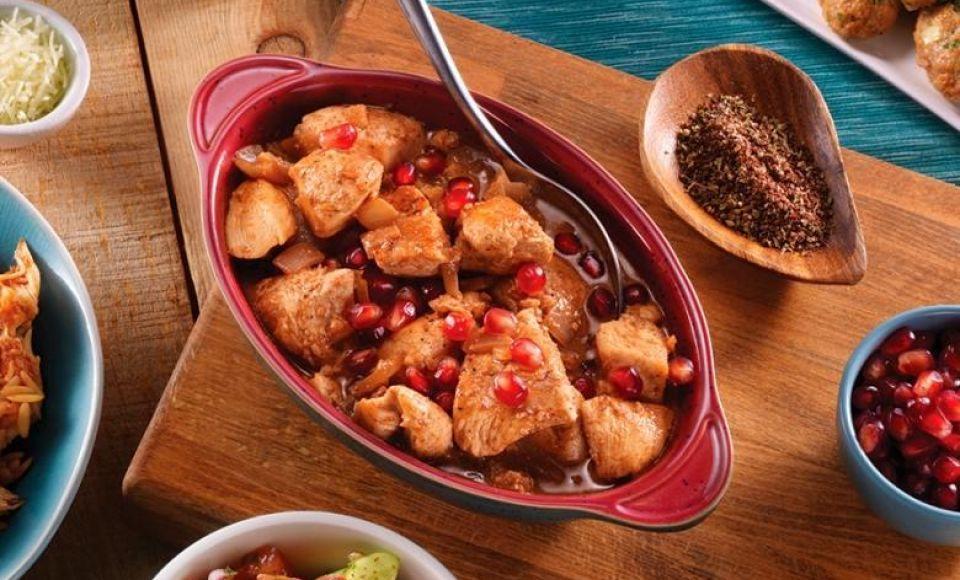 Kip met granaatappel en aardappelschijfjes in de oven