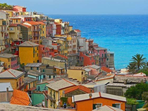 Een regenboog van huizen langs de kust van Ischia